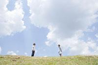 土手に立つ女子学生と男子学生 02299005961| 写真素材・ストックフォト・画像・イラスト素材|アマナイメージズ