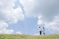手をつないで土手を歩く女子学生と男子学生 02299005962| 写真素材・ストックフォト・画像・イラスト素材|アマナイメージズ