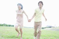 芝生を走る男女学生 02299005973| 写真素材・ストックフォト・画像・イラスト素材|アマナイメージズ