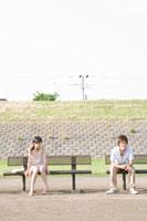 ベンチにすわる男女学生 02299005987| 写真素材・ストックフォト・画像・イラスト素材|アマナイメージズ