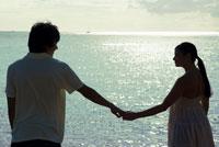 海辺で手を繋ぐカップル