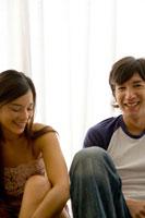 部屋に座り笑うカップル