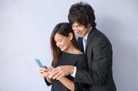 携帯を見て笑うOLとビジネスマン