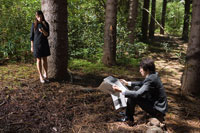 森の中で新聞を読む男性と携帯を見る女性