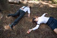 森で倒れるビジネスマンとOLと林檎