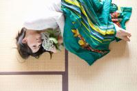 花を持ち畳に寝転がる女性