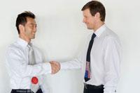 握手をする日本人と白人ビジネスマン