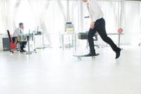 スケードボードで遊ぶビジネスマン