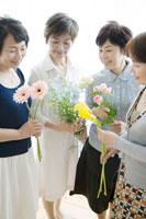 花を持ち見つめる中年女性四人