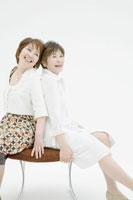 背中合わせにイスに座る中年女性二人 02299006330A  写真素材・ストックフォト・画像・イラスト素材 アマナイメージズ