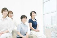 ソファに座る中年女性四人