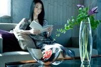 ソファに座り本を読む女性