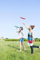 紙飛行機を飛ばす2人の女の子