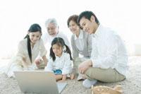 カーペットの上に座りパソコンを覗き込む家族5人 02299006810B| 写真素材・ストックフォト・画像・イラスト素材|アマナイメージズ