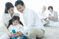 リビングで携帯電話を手にする親子3人とシニア夫婦
