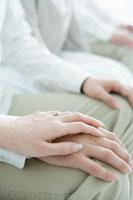 膝の上で重なる夫婦の手