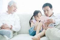 一緒にゲームをする父娘とそれを見る祖父