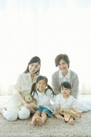 カーペットの上に座る家族4人 02299006911| 写真素材・ストックフォト・画像・イラスト素材|アマナイメージズ