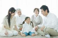 カーペットの上に集まる笑顔の家族5人