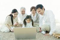 パソコンの前に座り画面を覗き込む家族5人