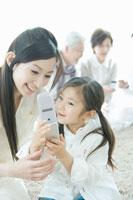 携帯電話を覗き込む母と娘