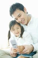 父の膝の上で携帯電話を手に持つ娘