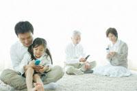 携帯電話を操作する父娘と祖父母