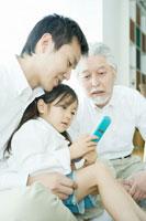 父の膝の上で携帯電話を手に持つ娘と祖父