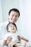 子供を膝の上に乗せる笑顔の父