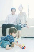 おもちゃで遊ぶ赤ちゃんと見守る夫婦