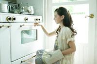 オーブンを開けようとする女性