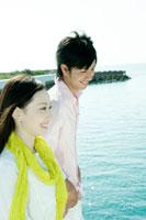 海沿いを歩くカップルの横顔