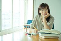 テーブルに肘をつき勉強する20代女性