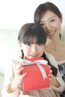 プレゼントを手に持つ娘と母 02299007193| 写真素材・ストックフォト・画像・イラスト素材|アマナイメージズ