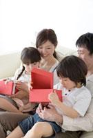 プレゼントの箱を開ける子供と両親 02299007195| 写真素材・ストックフォト・画像・イラスト素材|アマナイメージズ