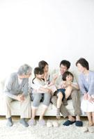 ソファでくつろぐ三世代家族
