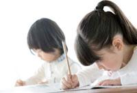 机に向かい勉強する男の子と女の子