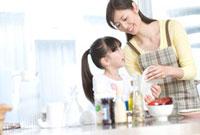 キッチンで一緒に皿洗いをする母と娘