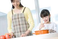 キッチンで母の手伝いをする娘