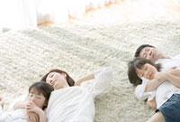 カーペットの上で寝転ぶ家族4人