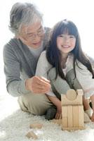 積み木で遊ぶ祖父と孫娘