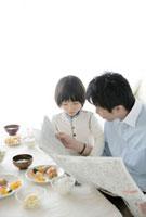 食卓で一緒に新聞を読む父と息子