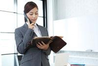 電話中に手帳を開くビジネスウーマン