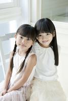 椅子に座り微笑む2人の女の子 02299007488| 写真素材・ストックフォト・画像・イラスト素材|アマナイメージズ