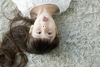 寝転び舌を出す女の子 02299007506| 写真素材・ストックフォト・画像・イラスト素材|アマナイメージズ