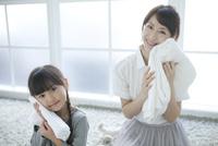 たたんだタオルを頬に当てる母と娘 02299007517| 写真素材・ストックフォト・画像・イラスト素材|アマナイメージズ