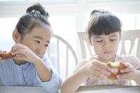 ドーナツを食べる2人の女の子 02299007536| 写真素材・ストックフォト・画像・イラスト素材|アマナイメージズ