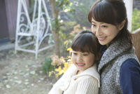 庭先で微笑む母と娘 02299007608| 写真素材・ストックフォト・画像・イラスト素材|アマナイメージズ