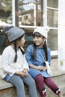 庭先で微笑む2人の女の子 02299007615| 写真素材・ストックフォト・画像・イラスト素材|アマナイメージズ