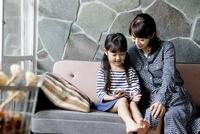 ソファで微笑む母と娘 02299007648| 写真素材・ストックフォト・画像・イラスト素材|アマナイメージズ
